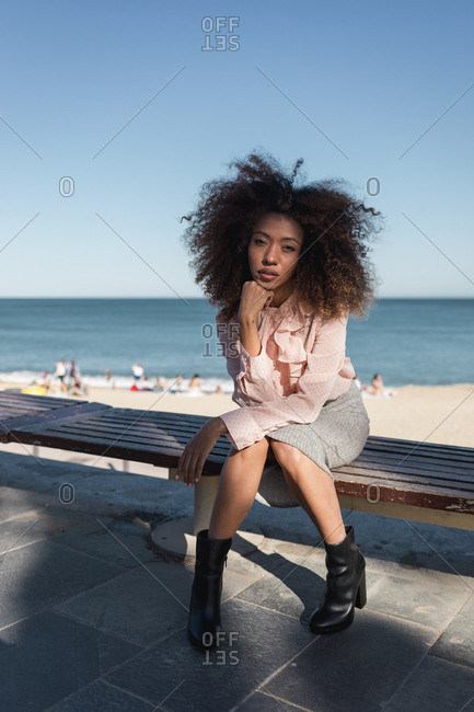 Portrait of beautiful young woman with afro hairdo sitting on a bench at the beach