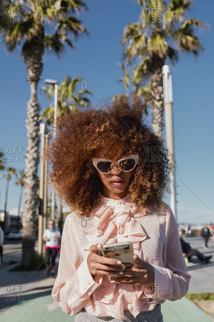 Stylish young woman using cell phone at seaside promenade