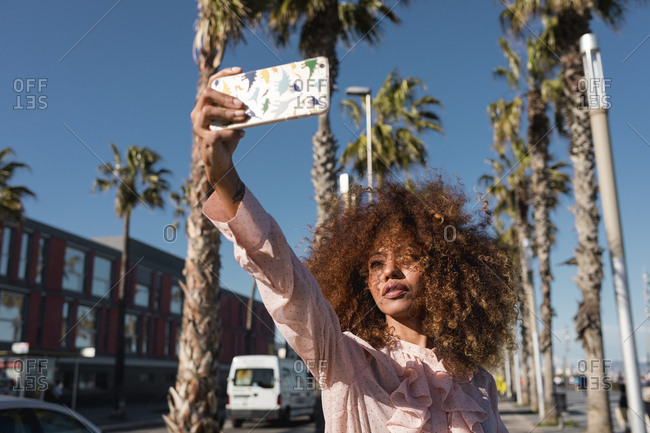 Stylish young woman taking a selfie at seaside promenade