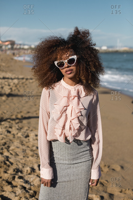 Portrait of beautiful young woman with afro hairdo standing on the beach