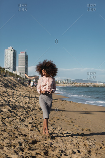 Young woman with afro hairdo walking on the beach