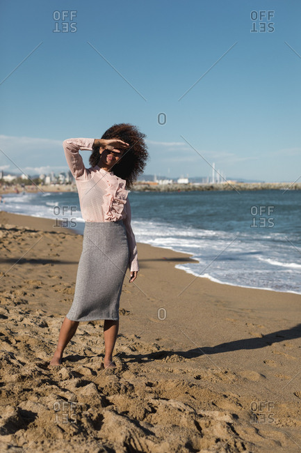 Young woman with afro hairdo standing on the beach