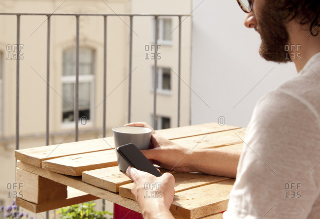 Man sitting with coffee mug on balcony using cell phone