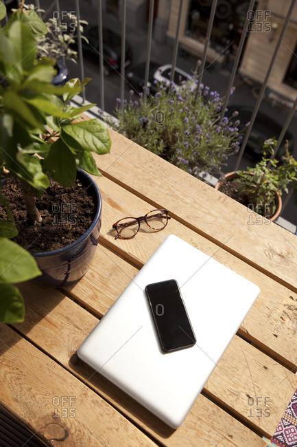 Smartphone- laptop and spectacles on palette on balcony