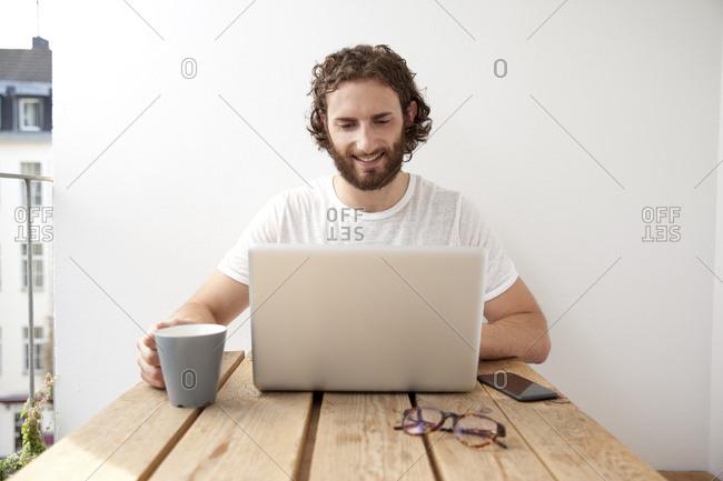 Portrait of smiling man sitting with coffee mug on balcony using laptop