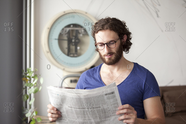 Portrait of young man reading newspaper in a coffee shop