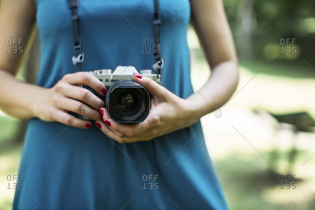 Woman's hands holding analogue camera- close-up