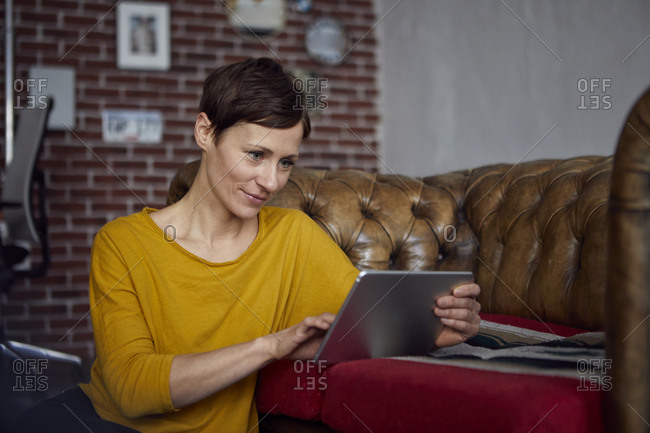 Woman sitting at home- using digital tablet