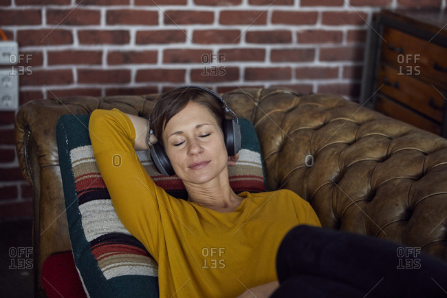 Woman with headphone lying on sofa- listening music