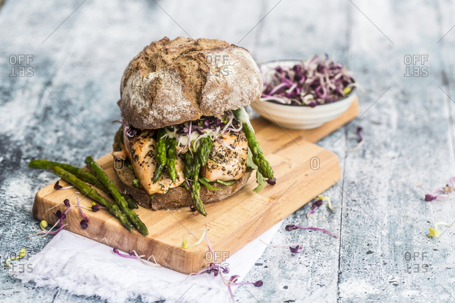 Salmon burger with green asparagus and red cress on chopping board