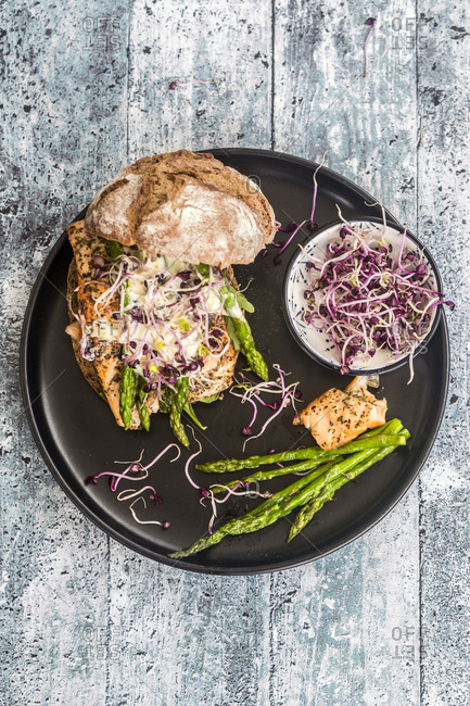 Salmon burger with green asparagus and red cress on plate