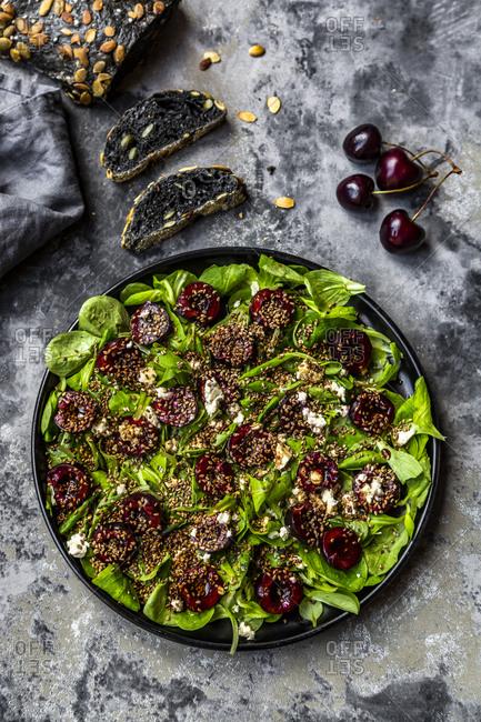 Lamb's lettuce with cherries- feta cheese- roasted sesame and black sepia spelt bread