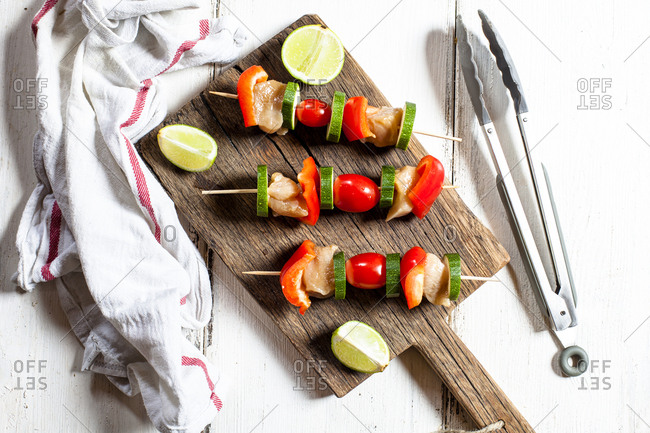 Grill skewers with raw chicken- tomato- bell pepper and zucchini on chopping board