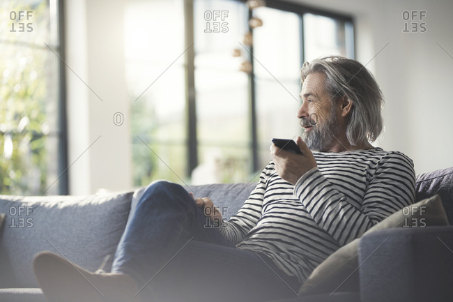 Senior man sitting on couch- using smartphone