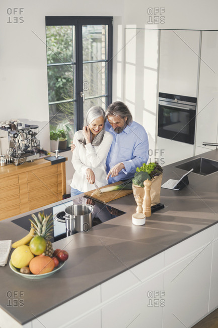 Happy senior couple preparing food in kitchen with online recipe