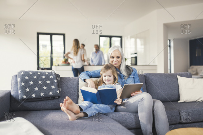Grandmother and granddaughter sitting on couch- reading together book and tablet pc