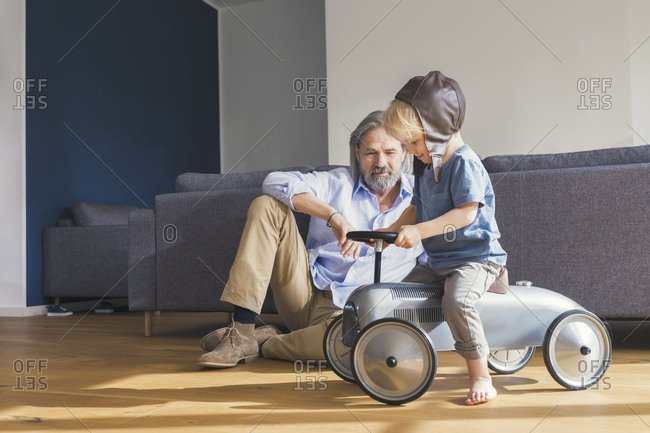 Grandfather playing with grandson- sitting on toy car