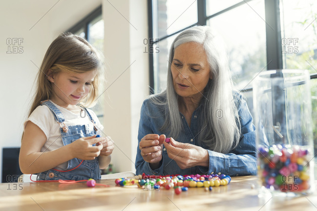 Grandmother and granddaughter threading beads