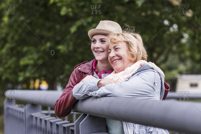 Happy grandmother and granddaughter leaning together on railing