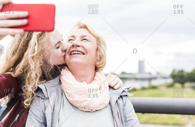 Grandmother and granddaughter taking selfie with smartphone
