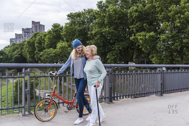 Grandmother and granddaughter strolling on a bridge