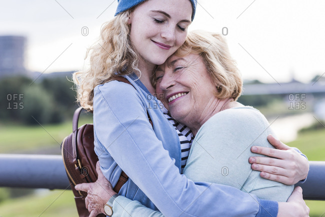 Happy grandmother and granddaughter hugging each other
