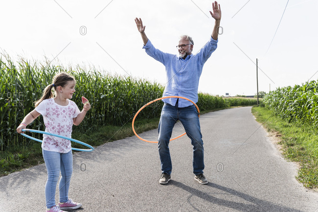 Grandfather and granddaughter playing with plastic hoop in the street