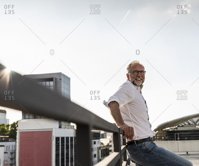 Mature man standing on roof of a high-rise building- leaning on railing