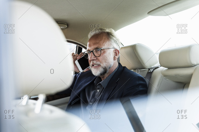 Mature businessman sitting on backseat in car- talking on the phone