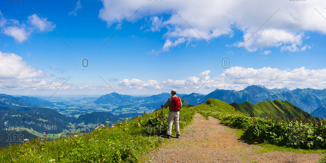 Germany- Allgaeu Alps- Hiker standing on path looking at panoramic road from Fellhorn to Sollereck mountain