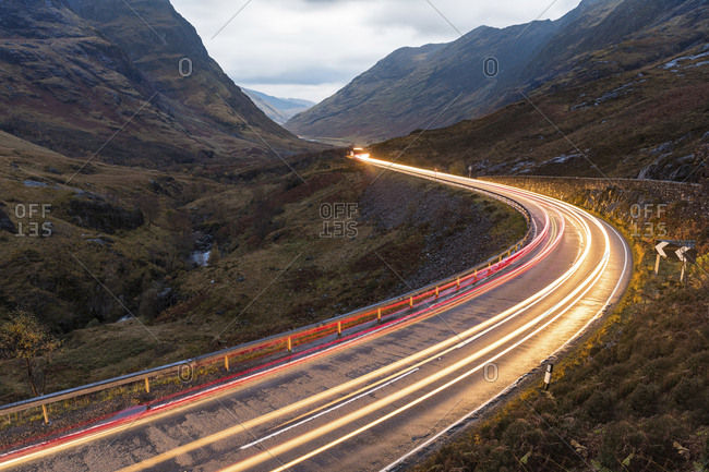UK- Scotland- car light trails on scenic road through the mountains in the Scottish highlands near Glencoe at dusk