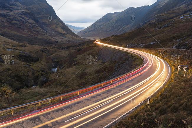UK- Scotland- car light trails on scenic road through the mountains in the Scottish highlands near Glencoe at dusk
