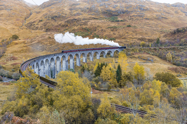 UK- Scotland- Highlands- Glenfinnan viaduct with a steam train passing over it