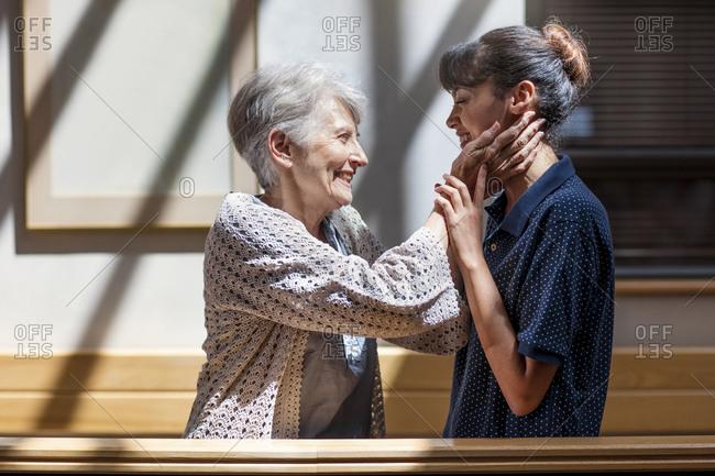 Nurse embracing senior woman in retirement home