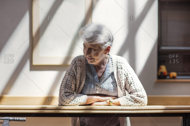 Lonely senior woman leaning on railing- looking down