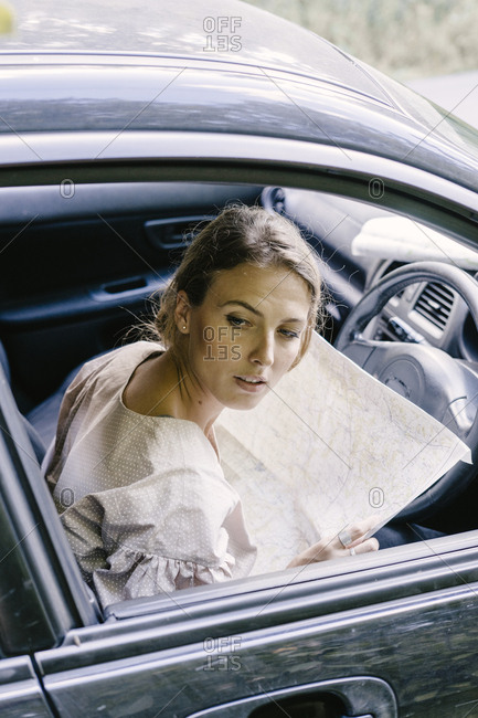Beautiful young woman in car with map