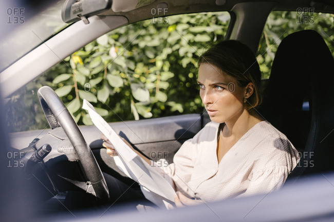 Beautiful young woman in car looking at road map