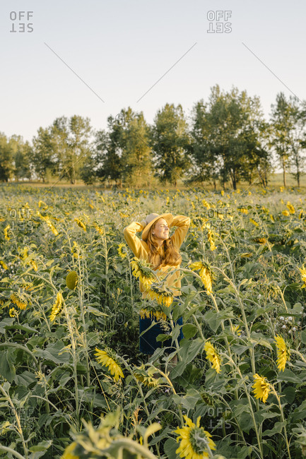 Woman in a straw hat smiling on the field with sunflowers