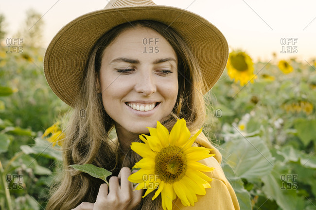 Portrait of a beautiful young woman is happy and smiling at the field of sunflowers