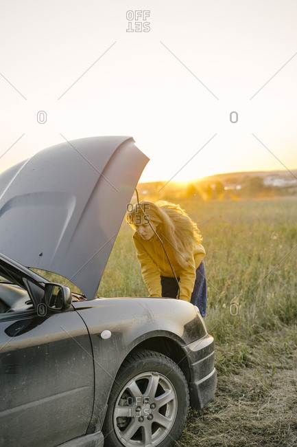 Young woman repairing a car engine outside the city