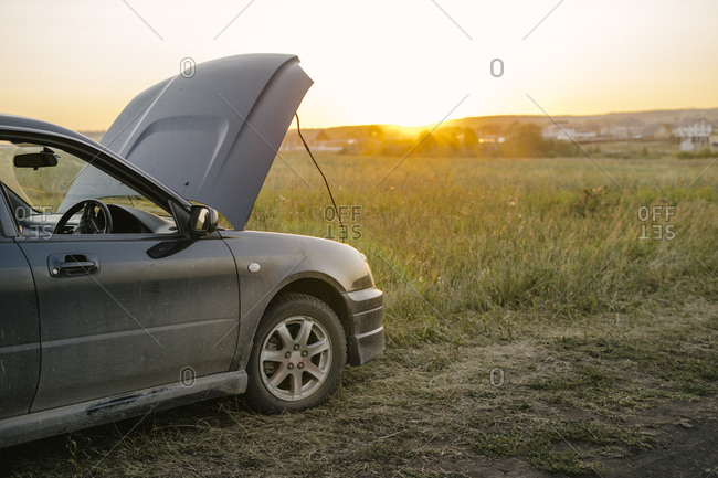 A car in a field outside the city at sunset