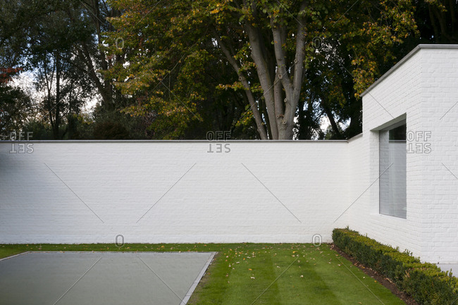 White wall in backyard of brick house