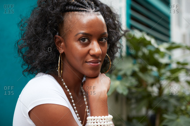 Young black woman sits outdoors looking to camera, close up