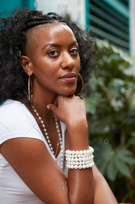 Young black woman sits outdoors looking to camera, vertical