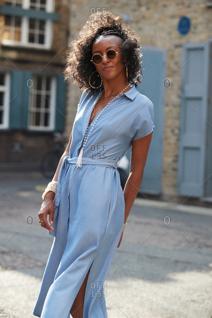 Trendy young woman in blue dress and sunglasses, close up