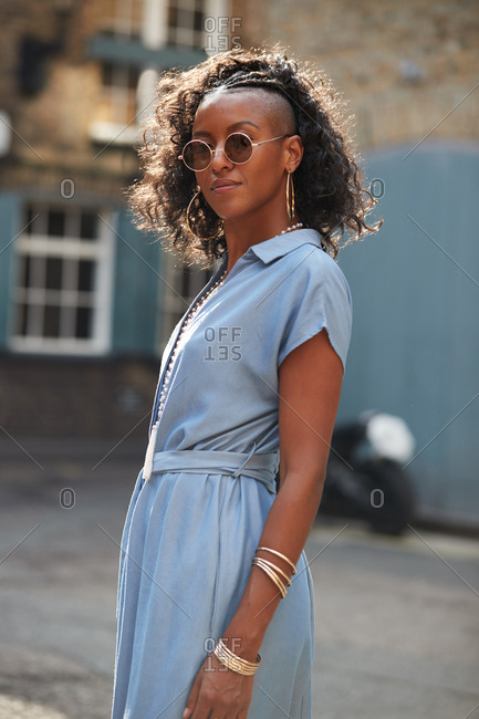 Fashionable young woman in blue dress and sunglasses