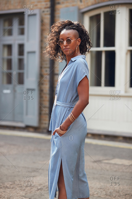 Trendy young black woman in blue dress and sunglasses