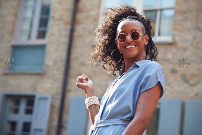 Trendy young woman in blue dress and sunglasses, outdoors