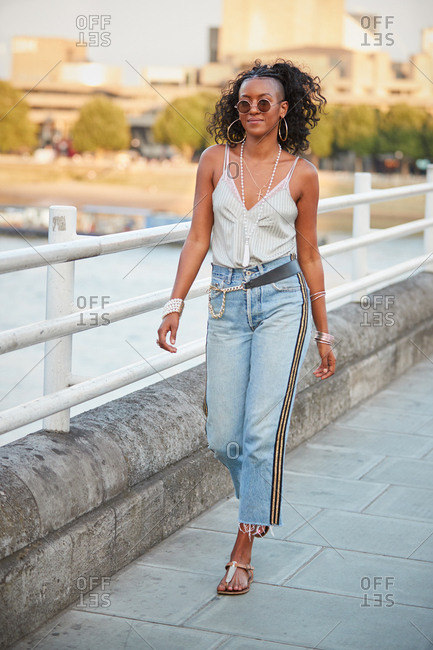 Trendy woman in striped camisole and side stripe jeans