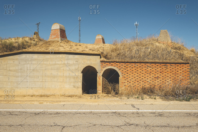 Main entrance and row of chimneys of ancient ceramic ovens in the middle of the road in Castile and Leon, Spain